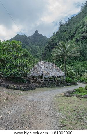 Grass Shack: grass shack, gravel road, lush landscape and mountains, at the Limahuli Garden and Preserve-National Tropical Botanical Garden, in Ha'ena, Halele'a, Kauai, mid-morning, on March 24, 2017