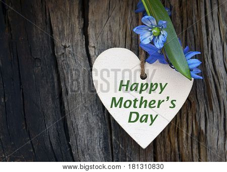Happy Mother's Day.Decorative wooden heart with first spring flowers on old wooden background.Mother's Day greeting card.Selective focus.