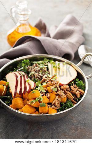 Healthy vegan grain bowl with quinoa, butternut squash, kale and apple
