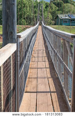 Let's Walk Across: looking across the historic suspension bridge in Old Hanapepe Town, on Kauai, Hawaii, mid morning, on March 28, 2017