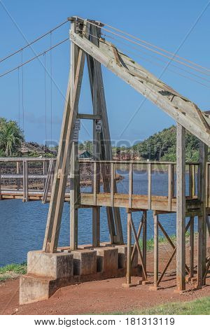 Wood and Cables: a partial view of one end of the swinging bridge in the historic town of Hanapepe, on Kauai, Hawaii, mid morning, on March 28, 2017