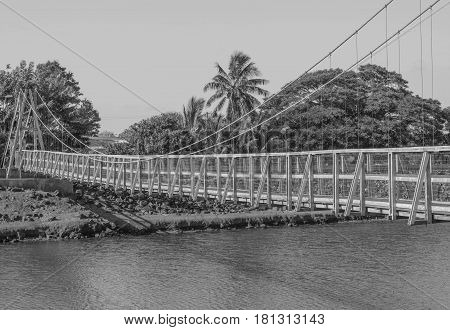 Swinging over a River: the historic swinging bridge in Old Hanapepe Town, in black and white, on Kauai, Hawaii, mid morning, March 28, 2017