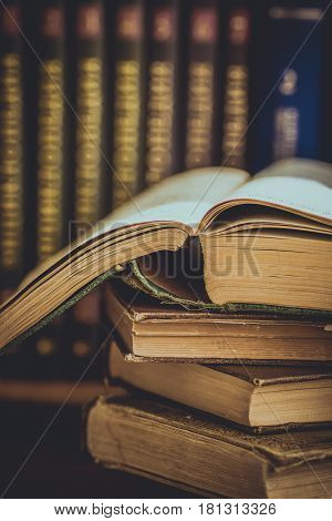 Pile of used old opened books volumes with impressed cover in the background, university education reading concept close up, toned