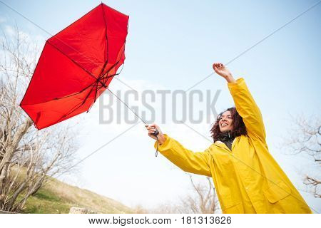 Young mulatte woman in yellow coat trying to catch flying red umbrella outdoor