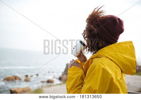 Woman in raincoat with coffee looking at sea on sunny day.