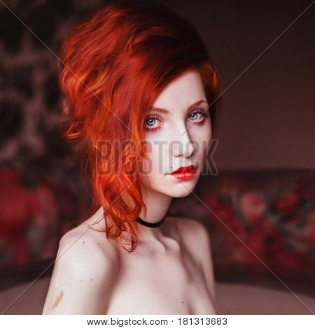 Woman with curly red background volosamina room. Red-haired girl with pale skin blue eyes a bright unusual appearance and red lips. Beautiful collarbone and neck