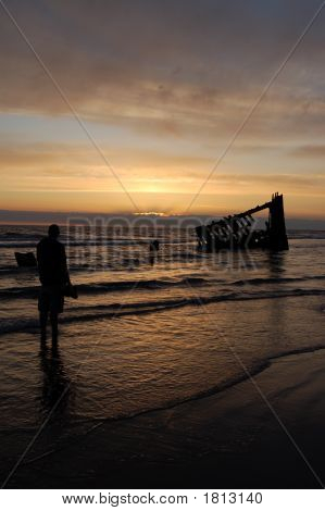 Silhouette Of A Man In Front Of Shipwreck At Sunset
