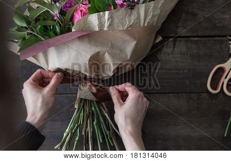 florist's hands covering flowers on wood background