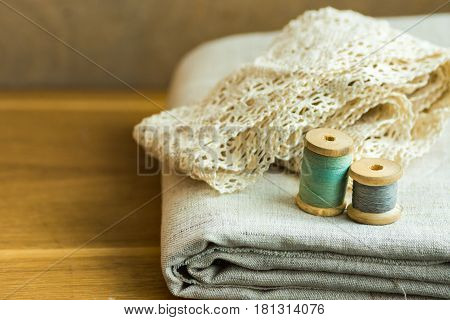 Folded linen fabric lace ribbons thread wooden spools on table sewing hobby fashion concept copyspace close up
