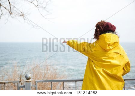 Woman in yellow raincoat showing at something at sea