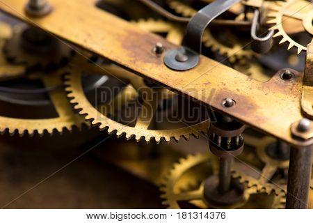 Clockwork. Old brass gears of clock mechanism. Shallow depth of field.