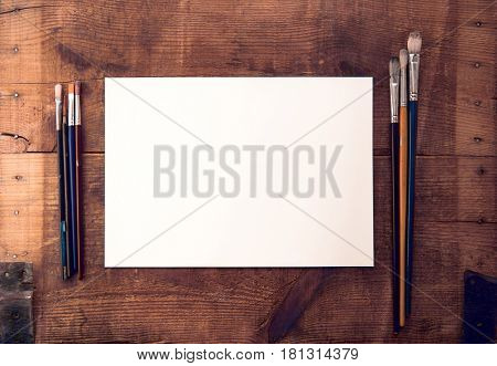 Blank white paper or canvas and painting brush on rustic and grungy wooden surface, with plenty of copy space. Nostalgic tone.