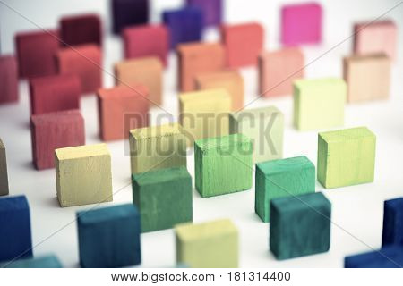 Wood blocks in different colors aligned and standing in muted tone, on white background.