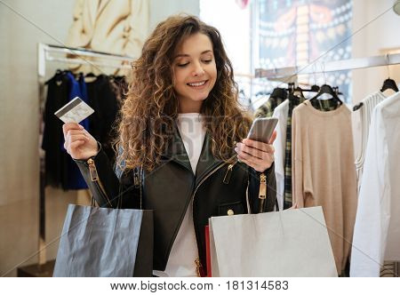 Image of cheerful curly young lady standing in women's clothing shop with shopping bags holding debit card. Looking aside and holding phone.