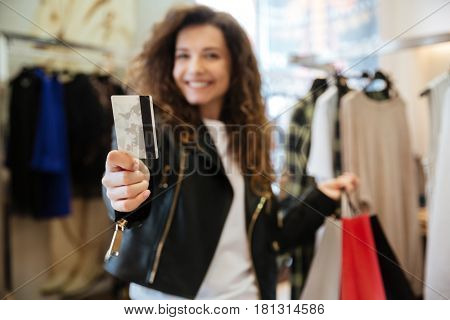 Picture of cheerful curly young lady standing in women's clothing shop with shopping bags holding debit card. Focus on card.
