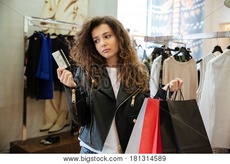 Image of sad curly young lady standing in women's clothing shop with shopping bags holding debit card. Looking aside.