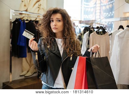 Photo of sad curly young lady standing in women's clothing shop with shopping bags holding debit card. Looking at camera.