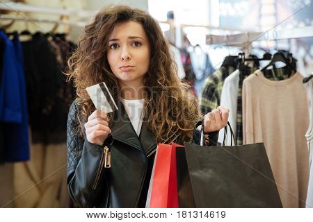Picture of sad curly young lady standing in women's clothing shop with shopping bags holding debit card. Looking at camera.