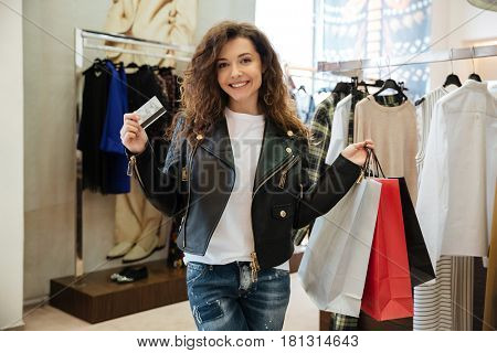 Image of smiling curly young lady standing in women's clothing shop with shopping bags holding debit card. Looking at camera.