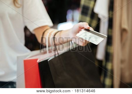 Cropped photo of young lady standing in women's clothing shop with shopping bags holding debit card.
