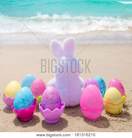 Easter bunny and color eggs on the sandy beach by the ocean - square photo Instagram format