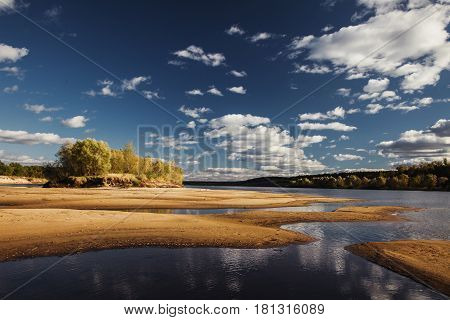Rest on the summer nature. Beautiful summer nature landscape. The bright clear blue sky with white clouds in summer nature. Yellow sand on the beach in summer nature. Water surface. The river on the plain. Green summer nature foliage. Wild summer nature.