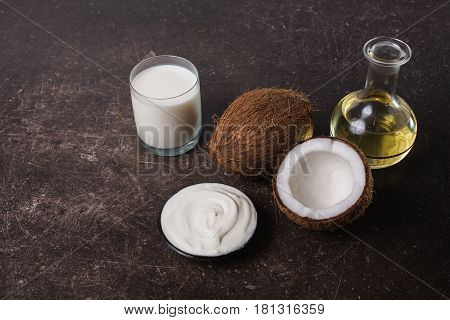 Coconut and coconut milk on a dark marble background. Exotic large walnut. Personal care. Spa treatments. Object on a dark background. Transparent object. Conceptual object. The objects are on the table. The object is on marble. The object lies on the sur