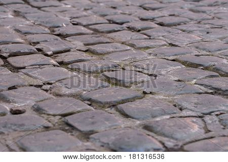 Close-up cobblestone pavement, stone street pavement background with selective focus. Stone road texture, cobblestones as a background