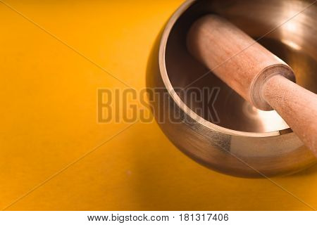 Metal bowl with a wooden stick on a yellow table diagonal horizontal