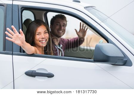 Happy multiracial couple on car travel together on summer vacation. Joyful young people smiling waving hello driving on road trip holidays. New young owners.