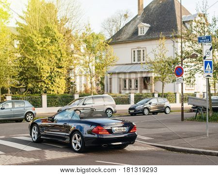 PARIS FRANCE - APR 7 2016: Man driving beautiful Mercedes-Benz SL-Class Cabrio Convertible open-top car - car crossing pedestrian walk in the center of the French city of on a summer day