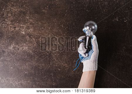 Hand in working gloves with a light bulb on a dark marble background. Object on a dark background. Transparent object. Conceptual object. The objects are on the table. The object is on marble. The object lies on the surface