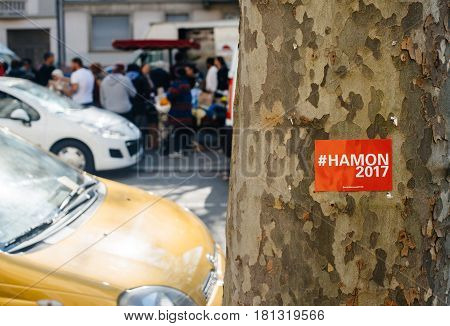 STRASBOURG FRANCE - APR 8 2017: Political agitation at French market for the upcoming French presidential election 2017 - Benoit Hamon 2017 sticker on tree with city market in the background