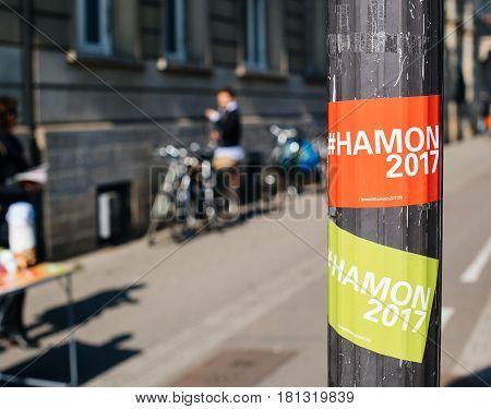 STRASBOURG FRANCE - APR 8 2017: Political agitation at French market for the upcoming French presidential election 2017 - Benoit Hamon 2017 sticker with city in the background