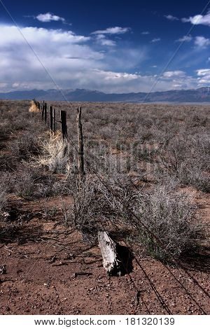 A fence line on the high prairie of the San Luis Valley near Alamosa, Colorado on a spring day