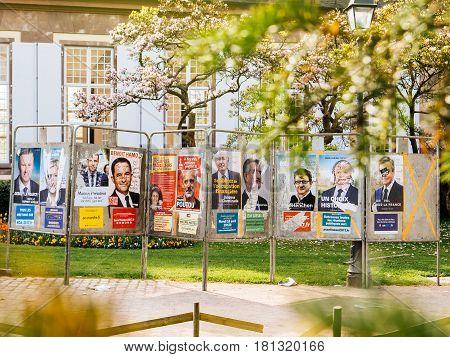 STRASBOURG FRANCE - APR 8 2017: Vandalized presidential elections campaign posters of Nicolas Dupont-Aignan Marine Le Pen Emmanuel MacronBenoit Hamon Nathalie ArthaudPhilippe PoutouJacques CheminadeJean LassalleJean-Luc MelenchonFrancois AsselineauFrancoi