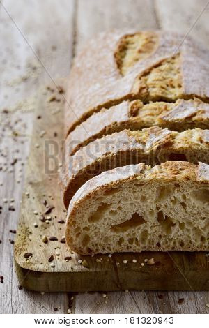 closeup of a loaf of spelt bread cut in some slices on a chopping board, placed on a white rustic wooden table