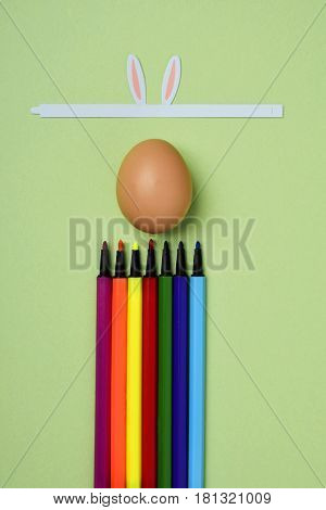 a brown egg with, a band with rabbit ears and marker pens of different colors on a green background