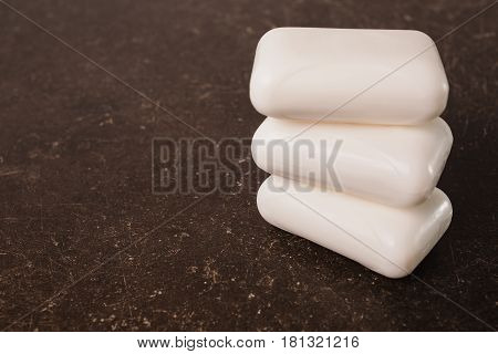 White soap on a dark marble background. Personal care. Hygiene. Object on a dark background. Transparent object. Conceptual object. The objects are on the table. Object on marble