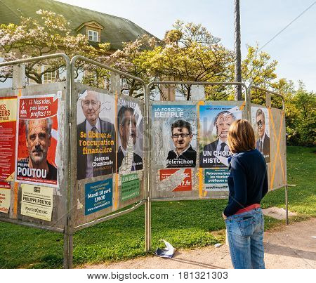 STRASBOURG FRANCE - APR 12 2017: Woman looking at official campaign posters of Jean-Luc Melenchon and other political party leaders of eleven candidates running in the 2017 French presidential election