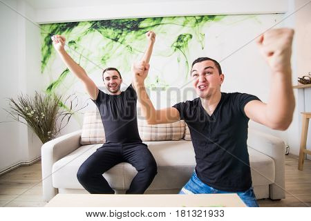 Two Excited Friends Or Roommates Watching Tv On Line Sitting On A Couch In The Living Room At Home
