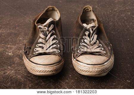 Old black sneakers on a dark marble background. Footwear for outdoor activities. Object on a dark background. Transparent object. Conceptual object. The objects are on the table. Object on marble