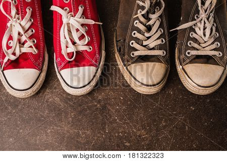 Old black and red sneakers and on a dark marble background. Footwear for outdoor activities