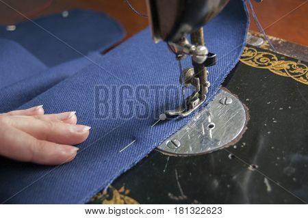 Sewing mashine with human hand pressing the blue tissue