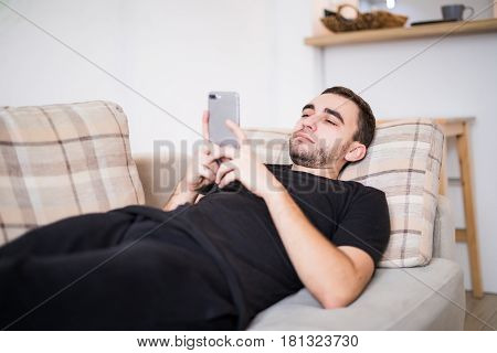 Young Smiling Man Surfing The Network And Text Messaging With Mobile Phone At Home
