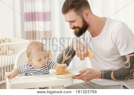 Handsome tattooed young man feeding cute little baby at home