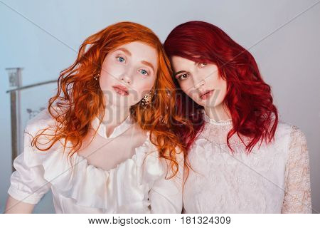 Two beautiful redhead girls with red hair in a beautiful white wedding Victorian dresses. Female style. The fragile redhead girl. Female portrait. Radhead models. Redhead  princess