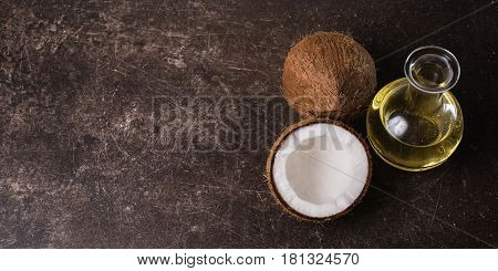 Coconut and coconut oil on a dark marble background. Exotic large walnut. Personal care. Spa treatments. Coconut concept. Coconut diet