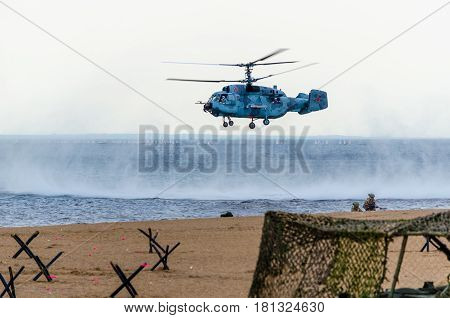A helicopter gunship hovered over the sandy coast, raising a spray and planting the landing of Marines on maneuvers. St. Petersburg, August 9, 2015.