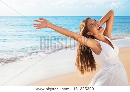Freedom woman on beach enjoying life with open arms feeling free bliss and success on beach. Happiness Asian girl in white summer dress enjoying ocean nature sunset during travel holidays vacation.